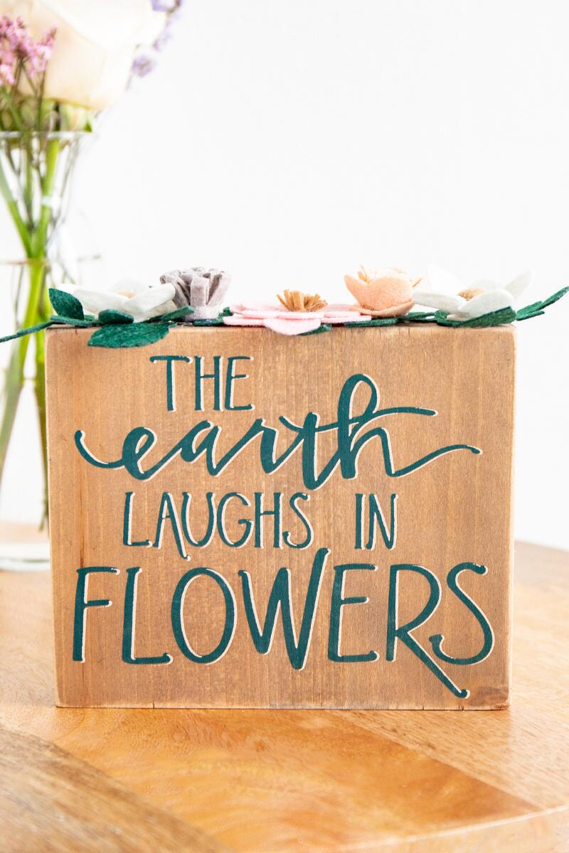 The Earth Laughs in Flowers Box Sign- Brown